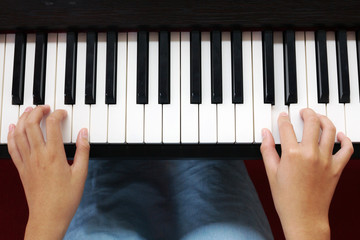 Teenage hands playing piano. Art and music background. Top view.