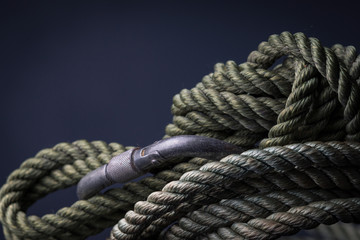 Green climbing rope coiled with carabiner