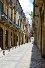 Deserted street of old European town on a clear Sunny day. The bright walls of the old town of Tarragona in Catalonia.
