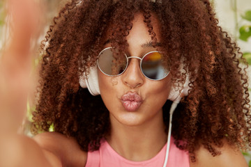 Fashionable woman with curly Afro hairstyle, makes grimace and poses for selfie, listens favourite radio or playlist in headphones. Cute dark skinned female enjoys broadcasting or good music