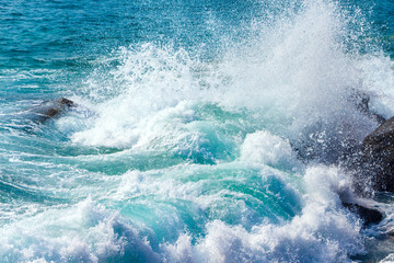 Beautiful turquoise wave crashing on rocks in tropical ocean with big splash. Close up.