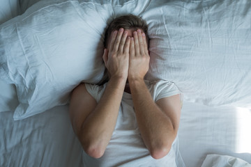 Caucasian young man closed eyes with hands in bed