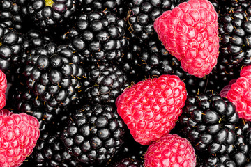Background pattern of close-up fresh picked blackberries and raspberries with leaves.