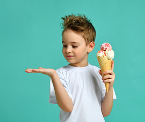 Baby boy kid hold strawberry ice cream in waffles cone on blue mint background