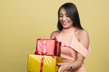 beautiful brunette female holding christmas presents, happy receiving birthday gift, isolated on studio yellow background