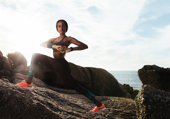 Female runner doing stretches at rocky beach