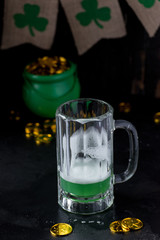 Saint Patrick's Day nearly empty mug of green beer with shamrocks and pot of gold in background