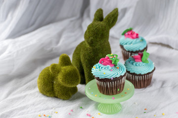 spring cupcakes in pastel colors with topiary baby bunnies on white background