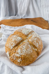 Easter Sunday cross cut bread on white cloth and wooden cutting board