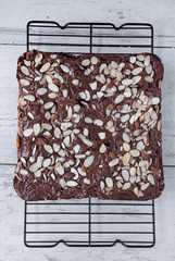 Brownies with almonds on baking rack on white table top view