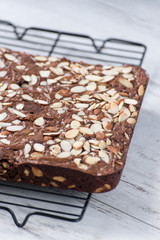 Brownies with almonds on baking rack on white table