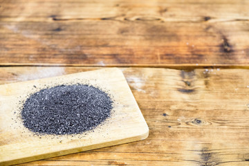 Black salt on wooden board. Wood background. Left on photo.