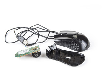 Dismantled computer mouse with USB cable on the white