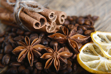 close-up anise star, scattered coffee beans, cinnamon sticks tied and dried lemon slices on wooden background, macro
