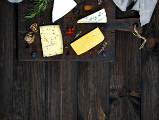 cheese on a brown cutting board: roquefort, brie, cheese with walnuts