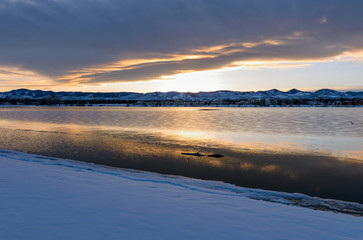 Stormy Winter Lake - A sunset view of winter storm clouds hanging over a snow and ice covered mountain city lake.
