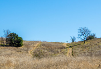 2 distant hikers on a rugged dirt path in rolling hills of Malibu, California