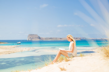 Relaxed woman enjoying sun, freedom and good book an beautiful sandy beach of Balos in Greece. Young lady reading, feeling free and relaxed. Vacations, freedom, happiness, enjoyment and well being.