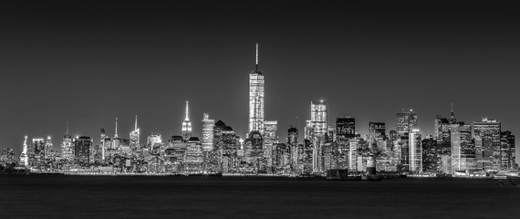 Fototapete - New York City Manhattan downtown skyline at dusk with skyscrapers illuminated over Hudson River panorama. Horizontal composition, black and white image.