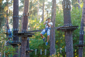 very cute and brave boy is in the adventure rope park. he will cope with all challenges!