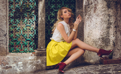 Vogue style elegant portrait of beautiful fashion woman wavy shine blonde long hair. Model in summer hat yellow skirt red shoes with bright makeup sitting in Ravello Amalfi coast city Italy background