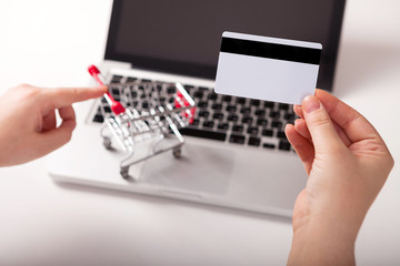 Woman forefinger pushing small shopping cart with Internet online shopping concept. Bank card nearby a laptop and mini shopping cart on white background top view.
