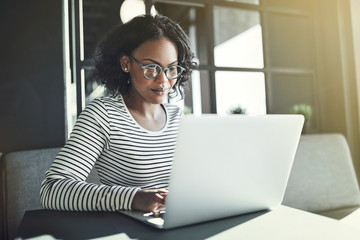 Young African woman sitting alone working on a laptop