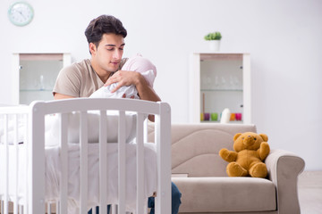Young father enjoying time with newborn baby at home