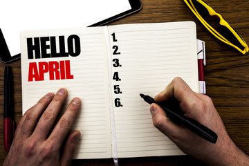 Word, writing Hello April. Business concept for Spring Welcome Written on book, wooden background with businessman hand, finger writing on the notebook.