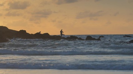 Wall Mural - Silhouette of a Fisherman on rocks against sunset sea in slow motion