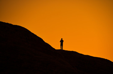 Silhouette of man on a rock watching the sunset