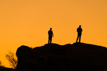 Silhouette of two men on a rock watching the sunset
