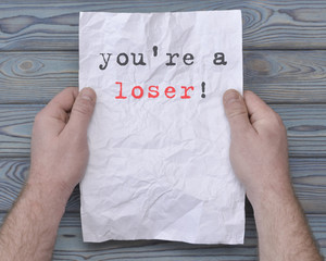 you're a loser! text on crumpled paper in the hands of a businessman. unemployed, dismissal, fax.