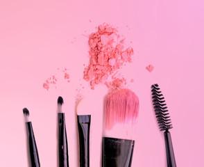 Brush make up set crushed make up power on pink background.