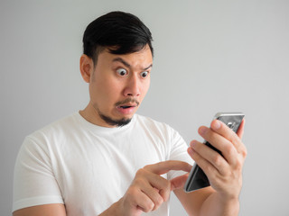 Shocked and scary face of man get yelled from smartphone.  See something scary in smartphone.