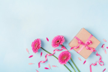Spring card for Birthday, Woman or Mothers Day. Pink flowers and gift box on blue table top view. Flat lay.