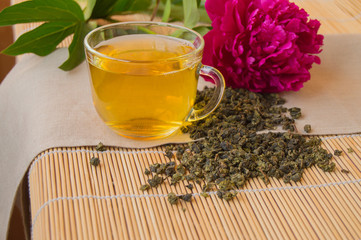 Cup of green tea, the leaves loose and peony flower