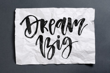 Dream big. Handwritten text on white crumpled paper. Inspirational quote.