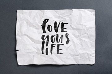 Love your life. Handwritten text on white crumpled paper. Inspirational quote.