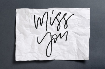 Miss you. Handwritten text on white crumpled paper. Inspirational quote.