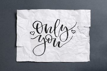 Only you. Handwritten text on white crumpled paper. Inspirational quote.