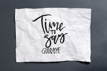 Time to say goodbye. Handwritten text on white crumpled paper. Inspirational quote.