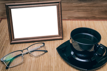 Blank photo frame with copy space, cup of black coffee and red alarm clock on office table background. Coffee break.