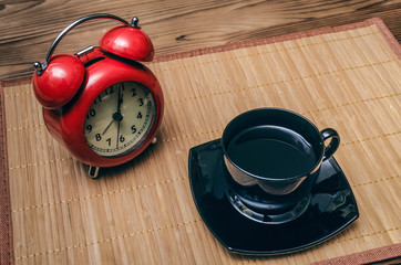Red alarm clock and cup of black coffee on office desk table background. Coffee break concept.