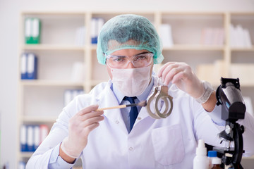 Criminologist police chemist looking at crime evidence