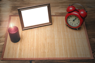 Photo frame with copy space, red alarm clock and burning candle on wooden desk table background with copy space.