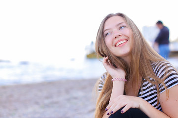 Portrait of charming female posing on camera, smiling and laughing, closing hair, sitting on sandy beach on background  blue bottomless sea on summer sunny evening. Young European-looking woman wit