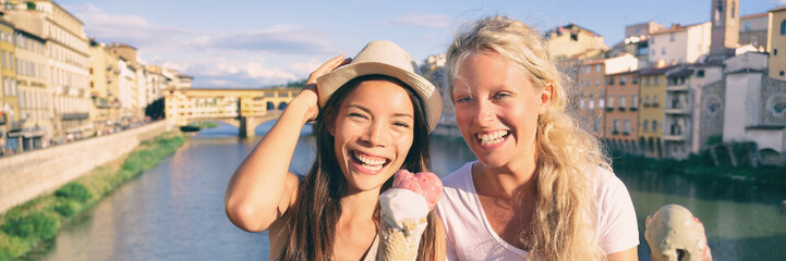 Travel tourists girls eating italian ice cream gelato cones on fun summer Italy vacation. Two young women in Florence, Europe tourism destination banner panorama.