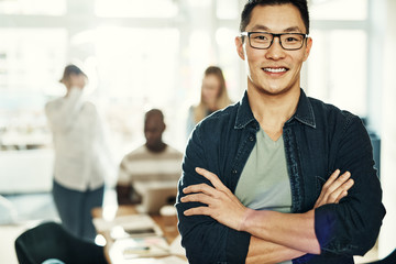 Young Asian businessman smiling with colleagues working in the background Wall mural