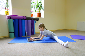 Blonde schoolgirl of European appearance sits on floor in cross-twist position and rewrites with friends through Internet on note. Child focuses on monitor and prints message. Concept of important for
